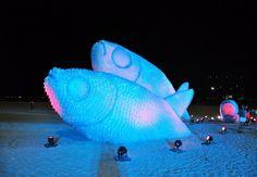 """Durante a Rio+20, conferência da ONU sobre desenvolvimentosustentável, uma obra de arte incrível foi instalada na praia de Botafogo, noRio de Janeiro. Feitos inteiramente de garrafas pet descartadas, os peixes sãoiluminados à noite e trazem os dizeres """"recicle suas atitudes""""."""