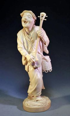 "Japan, Late 19th/ Early 20th Century, Meiji Period. Finely Carved And Incised Japanese Ivory Okimono Figure Of An Old Musician Holding A Stringed Instrument And A Straw Basket. Unique Open Mouth Expression, Inset Red Artist Seal Underside With Carving. 8""H"