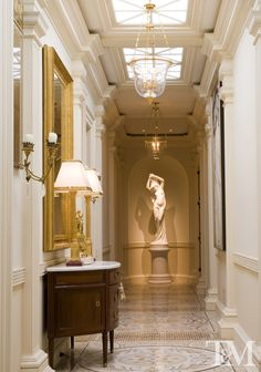 Very traditional and French Empire hallway with an elegant chandelier and mosaic granite flooring. They don't get much nicer than this.