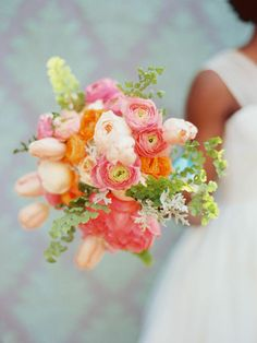 apricot and coral peonies, peach ranunculus, pink ranunculus, orange ranunculus, coral tulips, peach garden roses, dusty miller and maiden hair fern. tied with ribbon from Midori Ribbon.