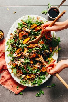Using salad tongs to grab some vegan Roasted Squash Salad with Nut Cheese and Balsamic Reduction