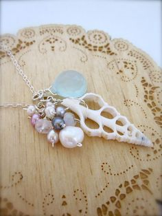 """$51.00 A beautiful large white sea shell slice is topped with a cluster of opaque white faceted moonstone and creamy white, peacock purple, mauve, bright pink, and silver pearls. It rests beside a stunning, sparkly seafoam blue faceted, heart chalcedony briolette. This pendant hangs slightly over 1 1/2"""" long. It hangs on a long, dainty sterling silver flat cable chain and closes with a sterling silver handmade clasp and tiny white pearl."""