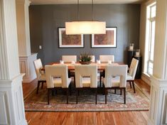 Traditional reeded columns surround this open-concept dining room that features a putty brown accent wall, contemporary upholstered dining chairs, table and lighting, all grounded by an Oriental rug.