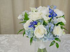 A layered garden designed bridal bouquet of white garden roses, white peonies, white mini calla lilies, and blue delphinium tucked in pale blue hydrangea and wrapped in antique white satin ribbon. Blue Delphinium, Blue Hydrangea, Blue Wedding Arrangements, White Peonies, White Gardens, Free Wedding, Calla Lily, Garden Design, Wedding Flowers