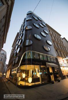 Im Mai 2013 hat das Erste der beiden Luxushotels für Lenikus, das Topazz in der Wiener Kramergasse, eröffnet. Eine Besonderheit sind die elliptischen Fenster in Ganzglas-Optik.  Aufgrund des Grundrisses mit den abgerundeten Ecken sind einige dieser Ellipsen und die Glasfassade im Erdgeschoß und Dachgeschoss noch dazu räumlich gekrümmt. Foto: Copyright @ Anna Blau Carports, Aluminium, Mai, Anna, Porch Roof, Attic, Floor Layout