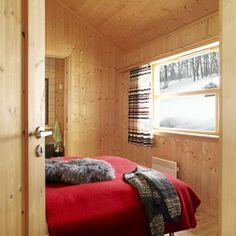 Hovedsoverommet er enkelt innredet med et rødt sengeteppe som blikkfang, det er også tilknyttet eget bad og badstue.