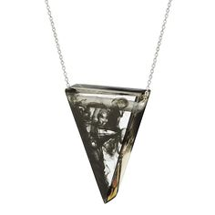 The triangular pendant is made from organic wood resin embedded with plumes of color.