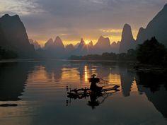 sunsetFishermen and osprey in Li River Guilin