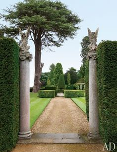 Stone columns crowned with 19th-century statues flank a gravel walk in the gardens at Easton Neston House, Northamptonshire, England. Photo by Oberto Gili. From Architectural Digest.