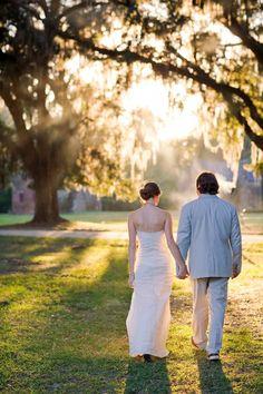 bride and groom walk away, backlit