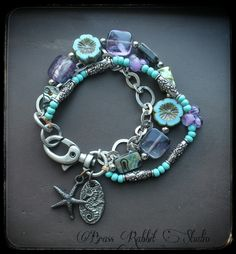 """Sky blue and purple triple strand bracelet with Abalone tabs, Czech glass flowers, amythest tabs, blue seed beads, and purple handmade lampwork Unicorn Beads. A little handmadepewter seahorse charm by Green Girl that reads """"Grace"""" on the backand a smallgunmetal starfish dangle near the clasp, a silver swivel base lobster clasp. this bracelet fits a 6.5""""- 7.5"""" wrist can be made larger if needed."""