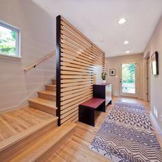 cloison en lattes de bois horizontales entre l'escalier de bois et l'entrée