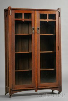 Arts & Crafts Bookcase  Oak  c. 1912  Two glass doors with mullions at top, with copper pulls, interior fitted with four shelves.