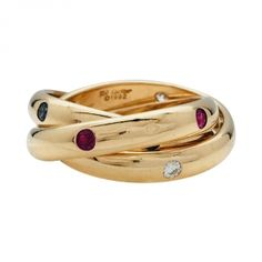 """Bague Cartier trois anneaux modèle """"Constellation"""" en or jaune, rubis, diamants et saphirs."""