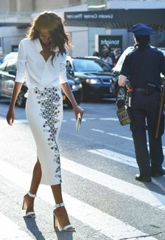 une jupe mi-longue de couleur blanc, femme marche sur la rue, cheveux bruns