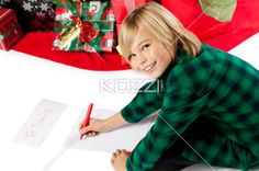 close-up of a boy writing a letter to santa. - Close-up portrait of a smiling boy writing a letter to Santa Clause for Christmas, Model: Josh Chapman