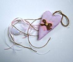 Μπομπονιέρα βάπτισης μαξιλαράκι που αποτελείται από απαλή, ριγέ, υφασμάτινη καρδούλα με κουμπάκι(διατίθεται σε 3 χρώματα, ροζ, λευκή και γαλάζια ) και 3 κουφέτα αμυγδάλου που κρέμονται από τις κορδελίτσες.Υλικό: ύφασμα, κορδέλες, σχοινίΔιάσταση: 11Χ7 εκ. (διάσταση καρδούλας)