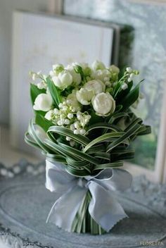 Amazing Bouquet Composed Of White Double Tulips, Lily Of The Valley, Green Foliage, & Woven Bear Grass Hand Tied Together With A Light Blue Silk Ribbon××××××××××××