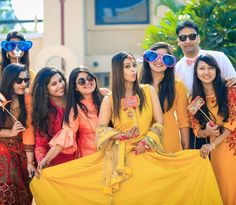 Bride with her Bridesmaids posing with fun props | Bridesmaids photoshoot ideas | Fun photos with Indian bridesmaids | Indian wedding Photography | Beautiful bride in yellow for her haldi | Bride tribe | Bride squad | Picture Credits: Happyframes | Every Indian bride's Fav. Wedding E-magazine to read. Here for any marriage advice you need | www.wittyvows.com shares things no one tells brides, covers real weddings, ideas, inspirations, design trends and the right vendors, candid photographers…
