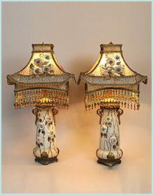 Pair of Austrian amphora bases which have been converted to lamps, hold a pair of Chinoiserie style PAGODA shades. The colors of the shades are cream and old with accent colors of pale blue, pale pink and  emerald green. The shades are covered in assorted antique metallic laces and old lame. The applied flowers mirror the flowers in the bases. Hand beaded fringe adorns the bottom.