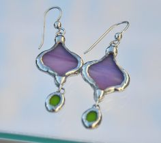 Purple and green hand crafted stained glass eastern petal drop earring are hand cut and ground to shape by eye. They are a modulated bright purple and apple green stained glass.  Edged in silver solder, with some beaded solder accents, notice the silver solder has a slightly hammered finish. Hanging from heavy gauge sterling silver French ear wire. The glass pieces hang 1 1/2 inch from the wire and are 3/4 Inch at the widest point.  Please inquire for other custom colors made to ord...
