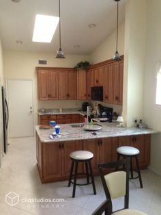 Small traditional Florida kitchen remodeled with granite countertops, black appliances, and raised panel kitchen cabinets from CliqStudios in the maple caramel jute glaze finish.