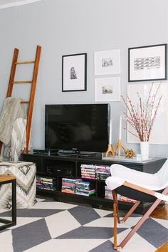 @Alaina Kaczmarski Chicago Apartment Tour // living room // grey // black // white // tv styling // @Euro Style Lighting butterfly chair // gallery wall // @Lulu & Georgia ankara pouf // ladder // photography by Stoffer Photography