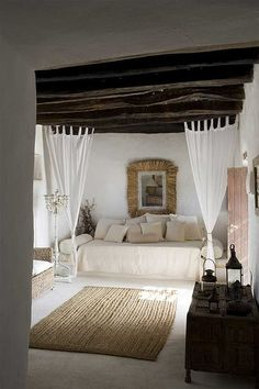 The textures and soft neutral pallete make this inviting and vacation-esque. The dark wood beams offset the soft airy curtains and creamy bed linens.