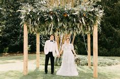 This wooden frame chuppah full of a lush canopy of greenery and pops of white blooms is breathtaking!!