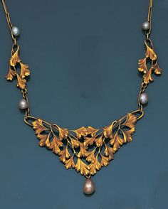 An art nouveau gold and baroque pearl necklace, by Henri-Victor Miault, circa 1905 Set to the front with a triangular engraved foliate lattice highlighted by baroque pearls, terminating in a baroque pearl drop of golden tint, on a chain of oval linking, signed Miault, indistinct maker's marks, French assay marks, pearls untested, 41.5cm