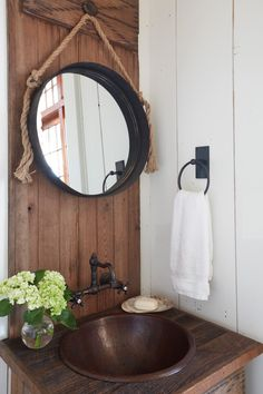 A hanging rope mirror is mounted against a rustic wood plank backsplash over a reclaimed wood washstand fitted with a hammered copper sink fixed beneath an oil rubbed bronze wall mount sink. Wood Plank Shelves, Wood Planks, Rustic Bench, Rustic Wood, Gold Grasscloth Wallpaper, Rustic Powder Room, Rope Mirror, White Shiplap Wall, Cabinet D Architecture