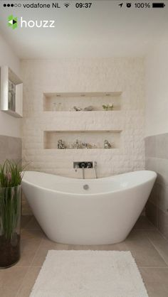 Small Bathroom with Stone Wall containing: Gray Tile Flooring with Freestanding Bathtub also Stainless Steel Towel Holder plus Glass Vase together with Fabric Bath Mat Spa Like Bathroom, Stone Bathroom, Amazing Bathrooms, Master Bathroom, Bathroom Ideas, Bathroom Vanities, White Bathroom, Small Bathroom, Seaside Bathroom