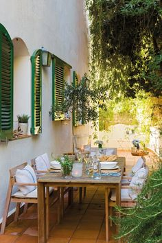 Love the outdoor entertaining area with green shutters and white walls and greenery