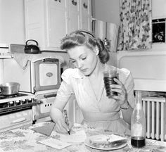 Vintage 1940's housewife in day dress, period 1940's kitchen, even a charming vintage lunch. Love the stove, floral curtains, and the fact that she is writing letters!