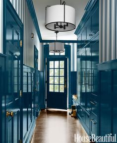 A very functional hallway lined with closets became a handsome mudroom once Harper lacquered the wainscoting and doors in Benjamin Moore's Twilight Blue.