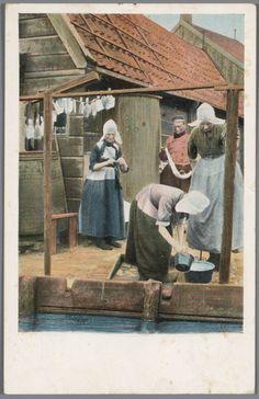 Man en drie vrouwen in Volendammer streekdracht. De middelste vrouw reinigt vaatwerk, de linker vrouw is aan het breien. 1894-1905 #NoordHolland #Volendam