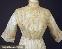 Pastel Embroidered Dress circa from 1913 made from handkerchief linen hand embroidered with blue polka dot at the background & stylized rose bands, handmade bobbin lace trim, silk cord & tassel belt, center back closure.
