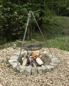 A very simple round fire pit created with rocks includes a hanging cooking grate suspended from teepee structure.