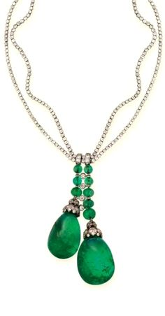A FINE ART DECO EMERALD AND DIAMOND NECKLACE, BY BOUCHERON Designed as two large emerald drops with diamond-set foliate caps to the emerald bead surmount with collet detail and two-row diamond line neckchain, circa 1925, 37.1 cm. long, with French assay mark for platinum, in cream leather Boucheron case Signed Boucheron.