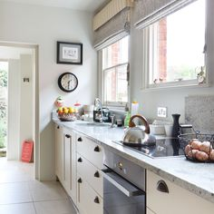 Small kitchen with neutral walls, cream cabinetry, grey granite worktop and grey flooring