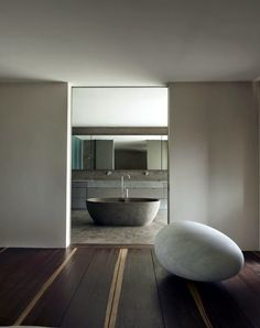 Design by Axel Vervoordt . Love the freestanding bathtub on the concrete floor.