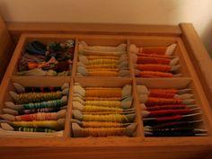 skrzynka z mulinami cieniowanymi, żółtymi, pomarańczowymi, czerwonymi. frędzle.