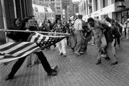 This is the Pulitzer Prize-winning 1976 photograph showing an anti-busing demonstrator attacking Ted Landsmark  with an American flag at city hall plaza in downtown Boston, during the  anti-busing dispute that struck the city in the 1970s. http://www.usnews.com/news/national/articles/2008/04/04/a-flag-a-busing-fight-and-a-famous-photograph