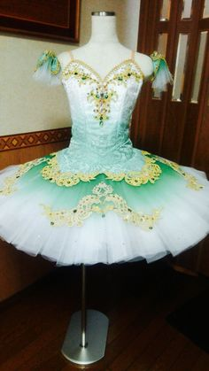 """This professional stage costume is one of our most sophisticated professional tutus. It has been entirely created using the """"ombre dyeing"""" technique, with graded fading colors. The bodice has been made using brocade fabric with fading white and green color. The decoration on the bodice is very rich, made using all kind of Swarovsky crystals, gold trims and sequins and emerald stones. The professional skirt fades from green to white and features a small green brocade overlay. Decoration on…"""