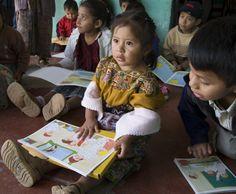 Niños en la escuela de la Aldea Sabalpop leyendo libros