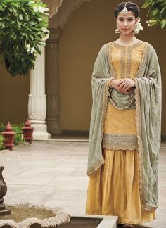 Yellow and Dusty Mint Green Gharara Suit features a silk jacquard blouse with santoon inner, cotton satin bottom and pure bemerg georgette embroidered dupatta. Embroidery work on this style is completed with zari, lace, stone and thread embellishments. Pakistani Suits, Pakistani Dresses, Indian Dresses, Pakistani Gharara, Punjabi Suits, Sharara Suit, Salwar Kameez, Anarkali Suits, Indian Wedding Outfits