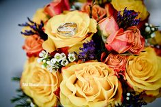 Bride and groom's wedding rings displayed on yellow, orange and peach rose bouquet.
