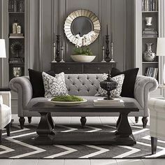 The classic gray sofa and black table plus the decor including the mirror at the back. Christian Grey, where are you?