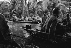 In a sudden monsoon rain, part of a company of about 130 South Vietnamese regional soldiers moves downriver in sampans during a dawn attack against a Viet Cong camp in the flooded Mekong Delta, about 13 miles northeast of Cantho, on Jan. 10, 1966. A handful of guerrillas were reported killed or wounded. (AP Photo/Henri Huet)
