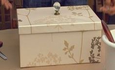 Storage box out of shoe box-covered in wall paper and knob added to top.  Could probably also decoupage scrapbook paper on to the box.  Cheap!:
